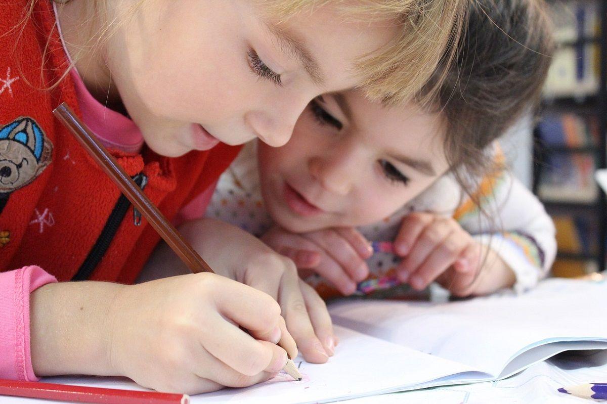 Zwei Mädchen schauen gemeinsam in ein Heft, in das eins der beiden schreibt.