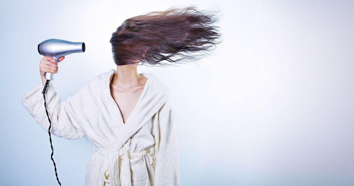 Frau hält einen Fähn vor ihre Haare sodass sie nach rechts wehen