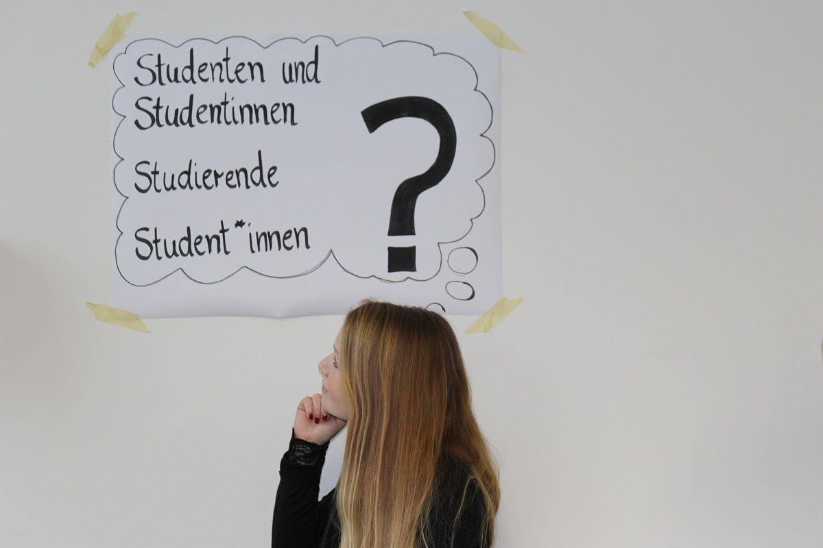 Eine Frau steht vor einem Plakat auf dem mehrere Fragen stehen
