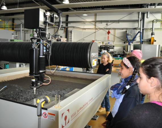 Mädchen stehen in einer Maschinenhalle. /Quelle: Gesche Neusel