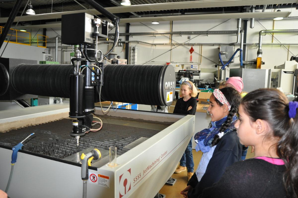 Mädchen stehen in einer Maschinenhalle. Bild: Gesche Neusel