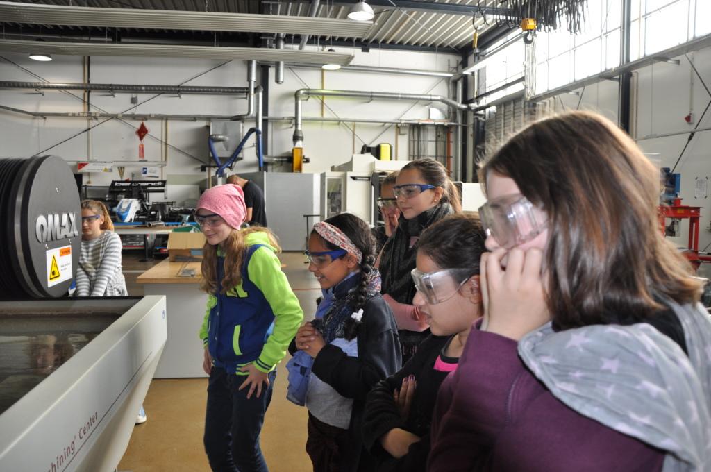 Mehrere Mädchen stehen in einer Maschinenhalle und halten sich die Ohren zu. Foto: Gesche Neusel