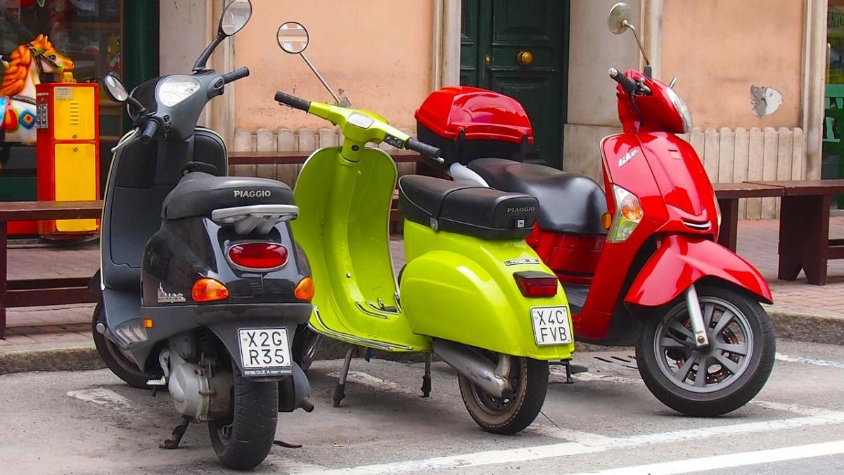 Drei Vespa-Motorroller in schwarz, grün und rot.