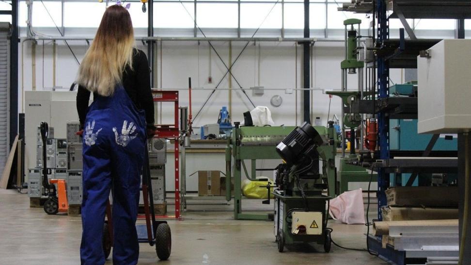 Eine Frau im Blaumann mit zwei weißen Handabdrücken auf dem Po in einer Maschinenhalle.