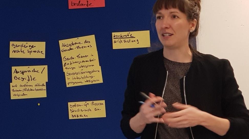 Lina Vollmer steht vor einer Pinwand mit Karten, auf denen maßnahme nfür eine geschlechtergerechte Lehre festgehalten sind.