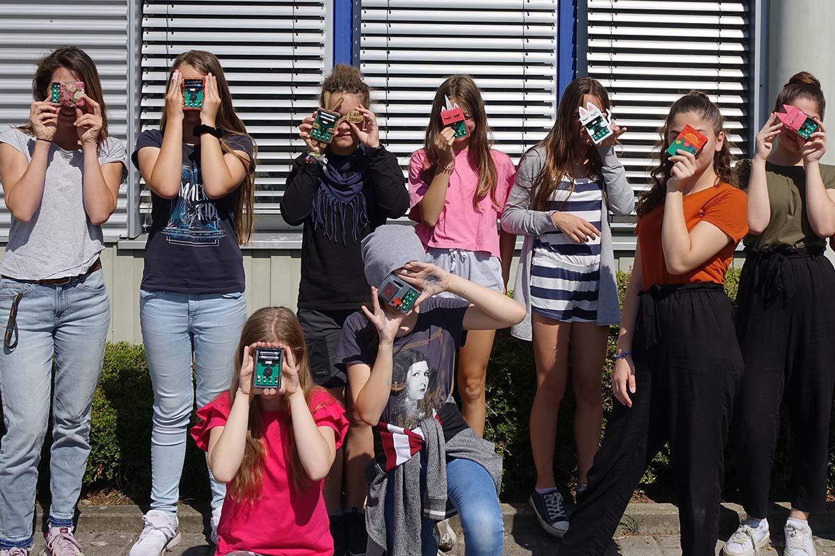 Gesche Neusel steht mit 7 Mädchen nebeneinander, sie halten sich selbstgebastelte Gameboys vor die Gesichter