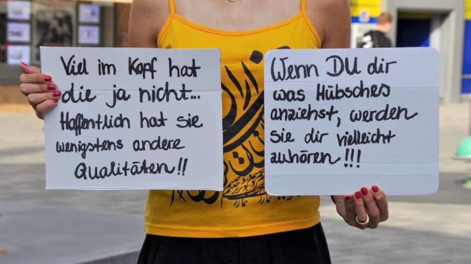 Eine Frau hält zwei Pappen mit Sätzen hoch, die an Klimaaktivistinnen im Netz gerichtet sind und sie aufgrund ihres Geschlechts kritisieren.