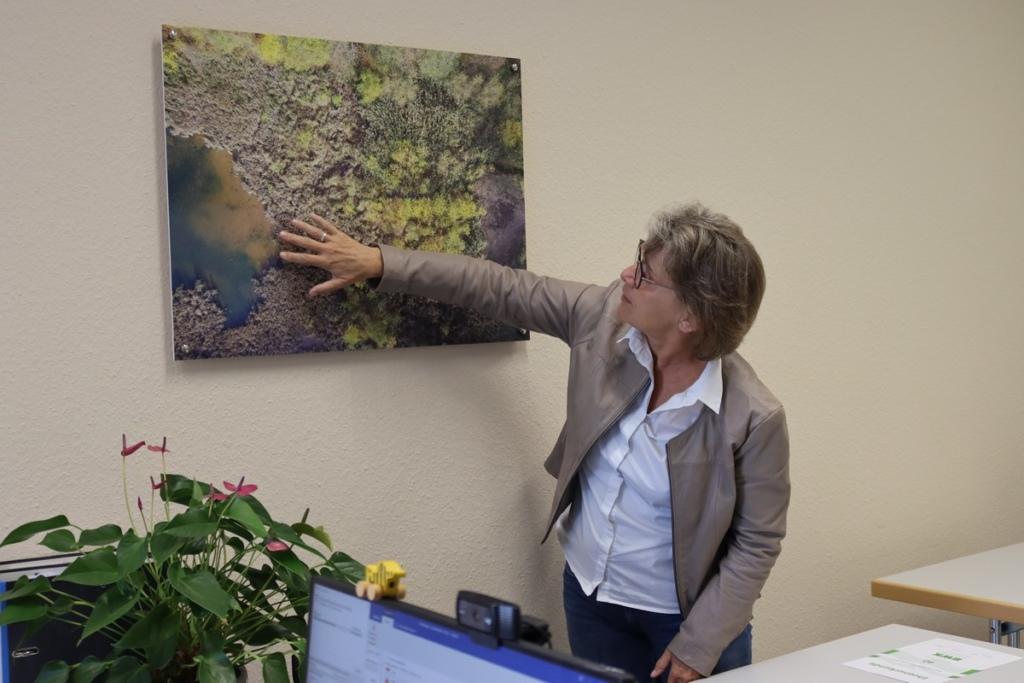 Martina Noethen zeigt in ihrem Büro eine Luftaufnhame eines Hochwasserrückhaltebeckes bei Eitorf.