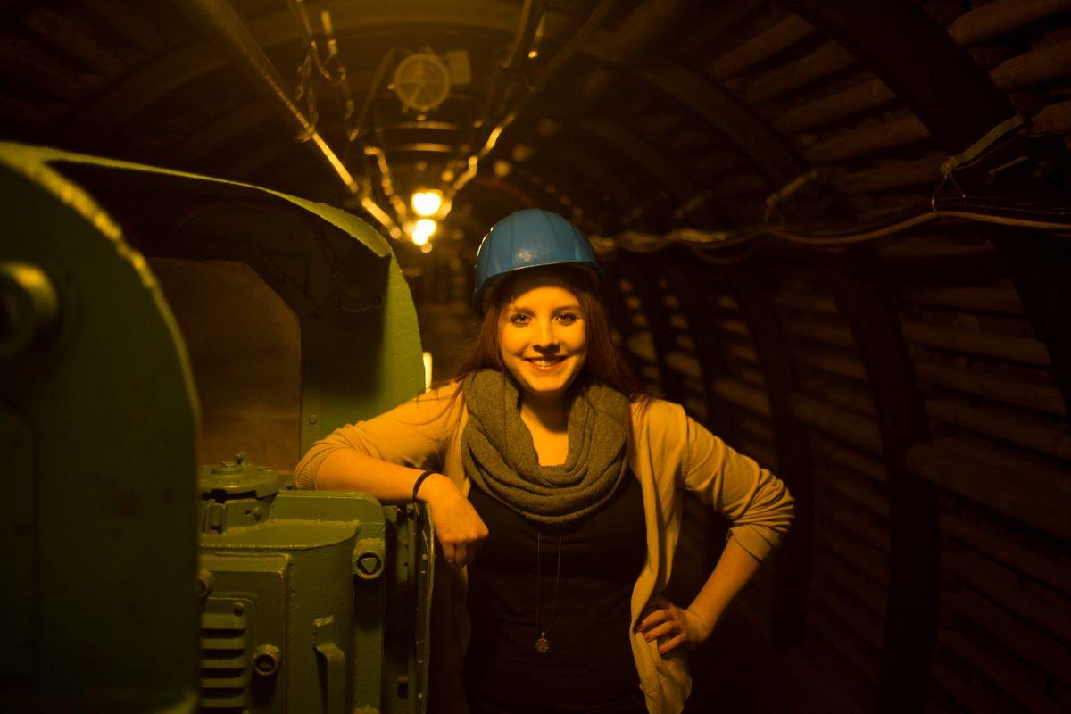 Eine Frau mit Helm in einem Bergstollen lächelt stolz in die Kamera
