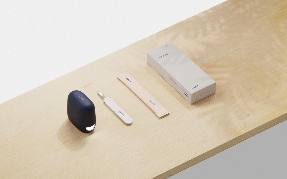 Das Gerät zur Bestimmung des Progesteron-Spiegels und ein Teststreifen liegen auf einem Regal.