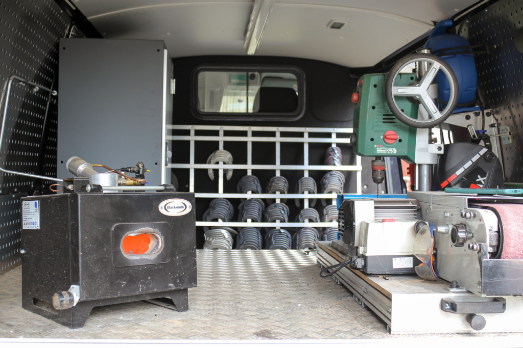 Ein Blick in den ausgebauten Transporter. Neben dem Schmiedeofen steht ein Bandschleifer und eine Standbohrmaschine. Im Hintergrund sieht man die Hufeisen-Rohlinge.