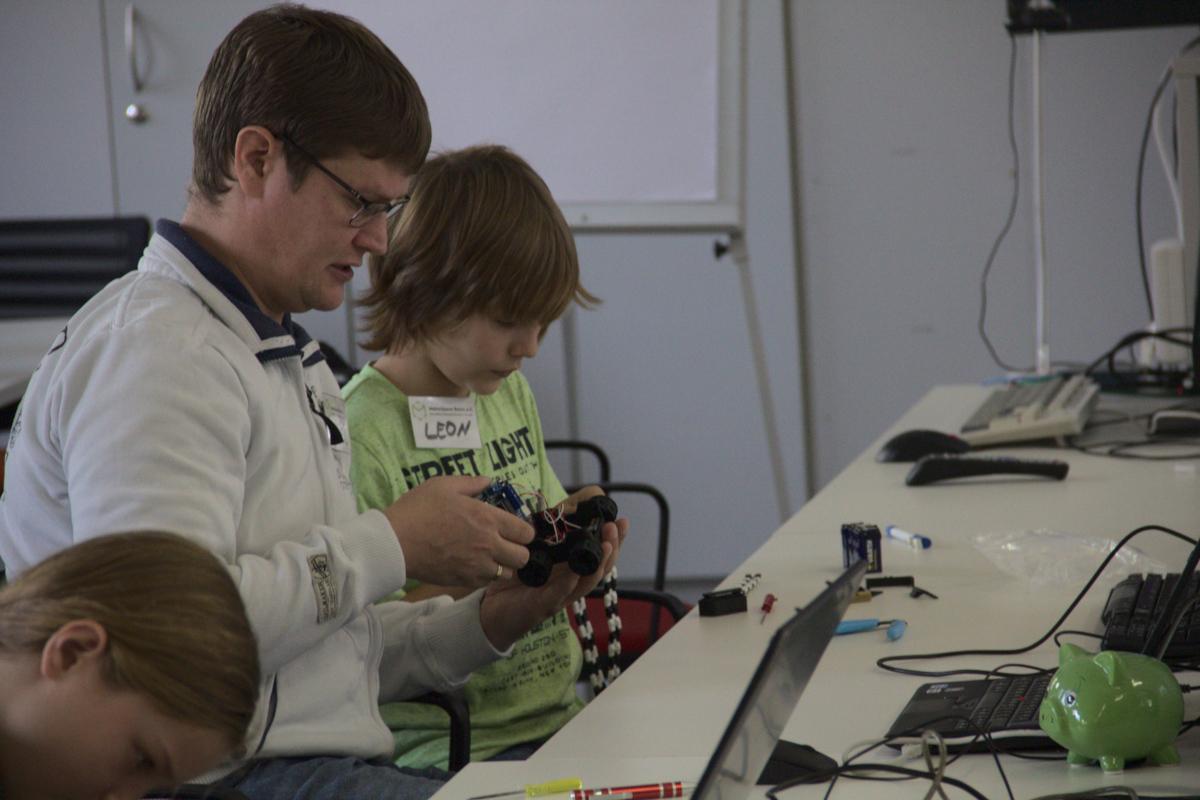 Ein Mann und ein Junge basteln im Makerspace gemeinsam an einem kleinen, programmierbaren Auto