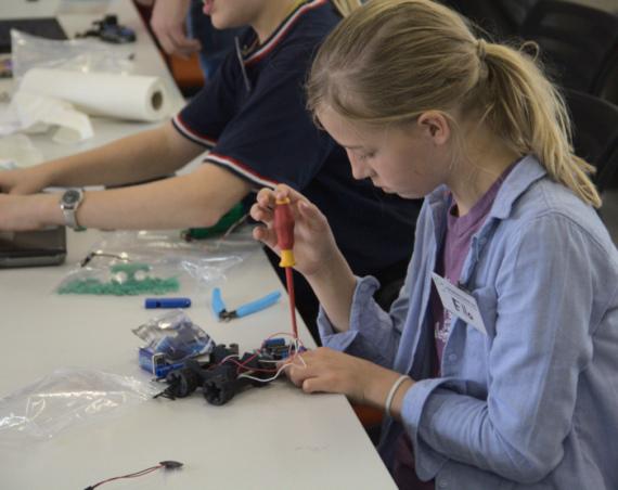 Ein Mädchen schraubt an der Elektronik eines kleinen, programmierbaren Fahrzeug.